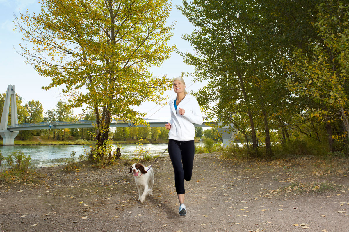 Lady and dog jogging along the Quarry Park river pathways